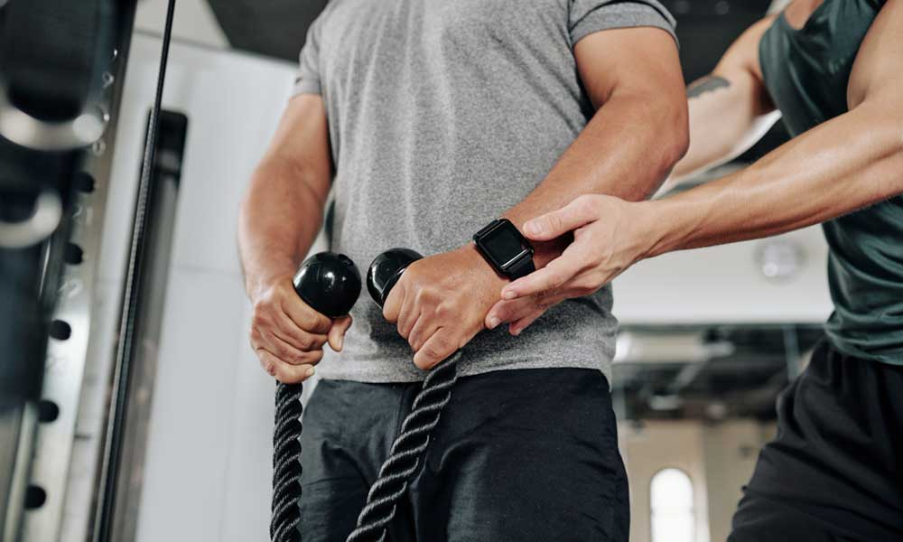 personal fitness trainer with a client in a gym