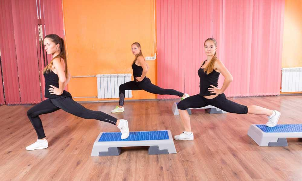 Teenage girls doing step aerobics for fitness and weight loss